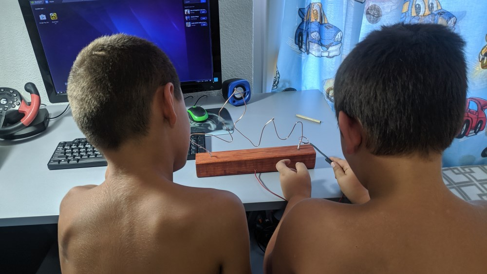 My son and his friend playing the wire loop game